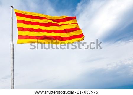 The flag of Catalonia - red stripes on a golden background - waving on the wind