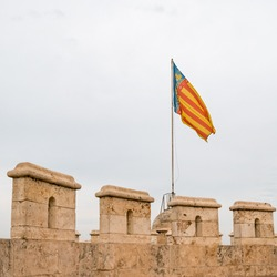 The flag of Communidad Valenciana on the top of Torres de Quart (ancient western city gate of old town Valencia).