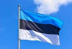 The flag of Estonia is a rectangular banner of three equal horizontal stripes of blue, black and white on a background of blue sky during the summer day.