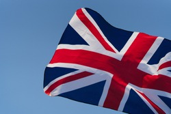 The flag of Great Britain develops in the wind at sunset against the sky. National symbol of England