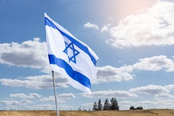 The flag of Israel on a field and a cloudy sky background. Memorial day-Yom Hazikaron, Patriotic holiday Independence day Israel - Yom Ha'atzmaut concept.