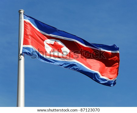 The flag of North Korea waving in the wind against a blue sky.