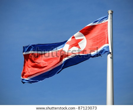 The flag of North Korea waving in the wind with slight vignetting for dramatic effect. - stock photo