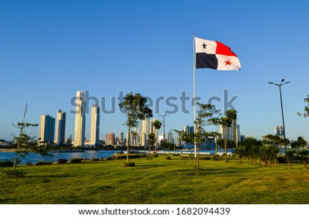 The flag of Panama hoisted on the mast, waving in the wind, in an open space covered with grass, behind the Pacific Ocean and view of the tall buildings of the city.