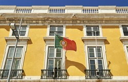 the flag of portugal waving to the wind in a building