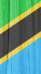 The flag of Tanzania on dry wooden surface, cracked with age. Mobile phone wallpaper with Tanzanian national symbol. Bright vertical background or backdrop