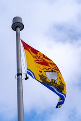 The flag of the Canadian province of New Brunswick (NB) flying on a flagpole.