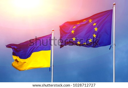 The flag of the European Union and Ukraine, against the background of the sunny sky. State symbols, politics. #1028712727