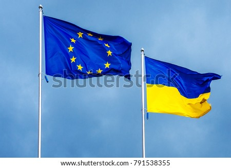 The flag of the European Union and Ukraine, against the background of the sunny sky. State symbols, politics. #791538355