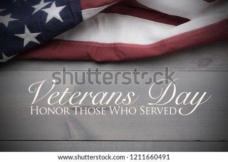 The flag of the United Sates of America on a grey plank background with Veterans Day greeting #1211660491
