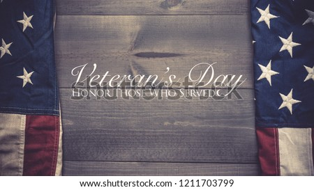 The flag of the United Sates of America on a grey plank background with Veterans Day greeting - Shutterstock ID 1211703799