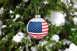 The Flag of the United States of America is depicted on a Christmas tree ball. Winter and New Year in the USA.