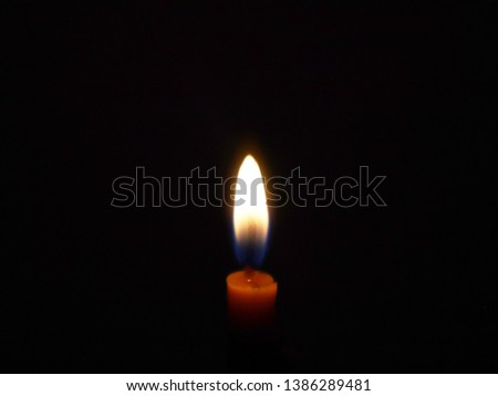 The flame of the candle glows behind the black.