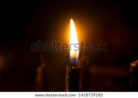 The flame of the candle glows in the blur background.
