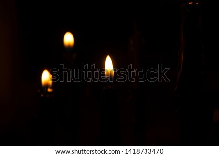 The flame of the candle glows in the night.