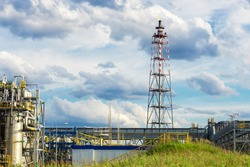 the flame of the torch of the oil and gas industry stands out against the background of the blue sky and clouds and is part of the technological block