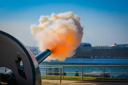 The flash of cannon being fired as cruise ship deoarts harbour.