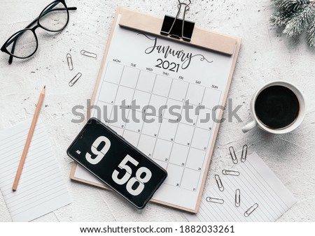 Photo of  The flat lay of a calendar diary, flip clock screensaver on the phone, mug, glasses, clips, and pencil, the concept of a fresh start in the New Year