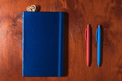 The flat lay view of blue notebook,  red and blue pens on brown table. The pens and notepad are on the desk.