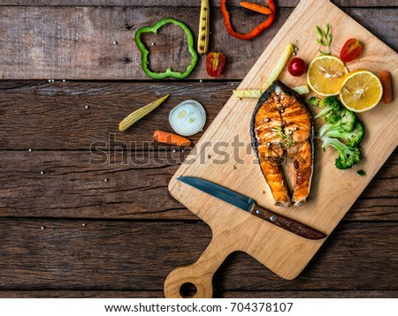 The flatlay food image of preparing Salmon Teriyaki with variety kinds of vegetable on a wooden chopped board on a wooden table #704378107