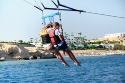 The flight of a mother and son on a parachute over the water. The concept of active recreation