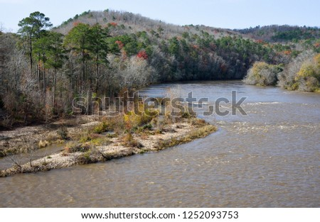 The Flint River at Sprewell Bluff Park in Thomaston Georgia USA works its way through mountains and valleys as it flows toward the Gulf of Mexico. Autumn leaf color in the surrounding hills. #1252093753