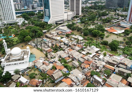The flooded street in a poor residential district in the heart of Jakarta city in Indonesia capital city which show huge inequalities with modern towers surrounding it