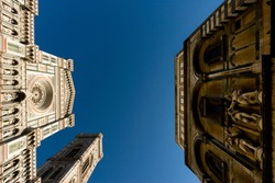 The Florence Cathedral (Duomo di Santa Maria del Fiore), the Giotto's Campanile and Florence Baptistery (Battistero di San Giovanni) facing each other on a sunny day.