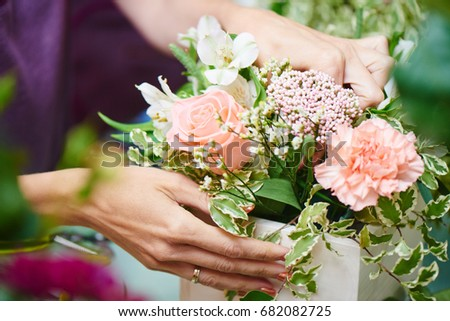 The florist makes the bouquet top view on background white Board #682082725