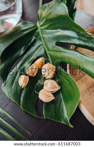 The flowers of the physalis lie on a leaf of a tropical plant, on a wooden table next to a glass vase and a wooden plank