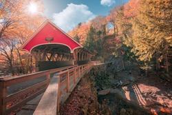 the flume covered bridge in Lincoln, New Hampshire with sun glare and autumn colors