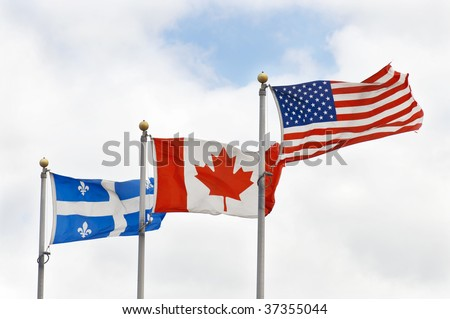 The fluttering in the wind, the flags of USA, Canada and Quebec on the background of the cloudy sky.