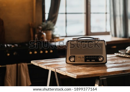 The FM channel is playing music, a stylish retro radio player stands on a wooden table. stylish kitchen in the village, daylight from the window. copy space