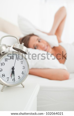 The focus on the clock as it rings causing the girl to cover her ears with a pillow.