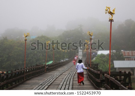 The fog on the bridge, the Mon Bridge, or the Uman Manusorn wooden bridge, the longest wooden bridge in Thailand in Sangkhlaburi, Mon people are selling flowers in the winter.