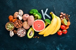 The food contains natural potassium. K: Potatoes, mushrooms, banana, tomatoes, nuts, beans, broccoli, avocados. Top view. On a black background.
