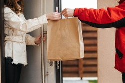 The food delivery man passes the craft package to the customer at the door of her house