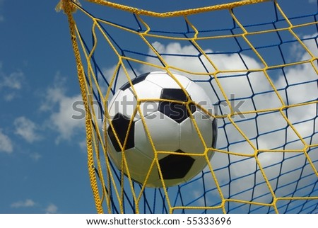 the foot ball in mesh of goal on background of clouds