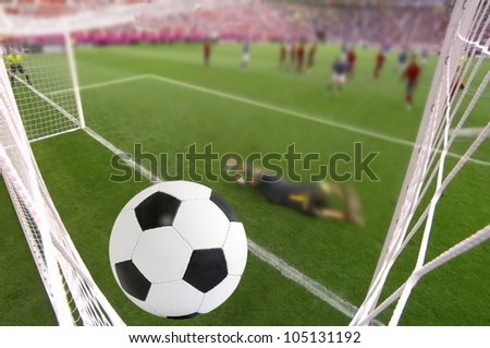 the foot ball in mesh of goal on background of stadium