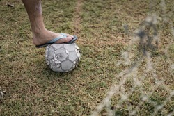 The foot of football player put on the old football in the grass field with the foreground of broken old goal net. Concept of people and sport in poor country.