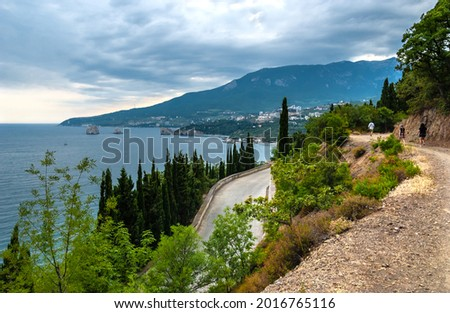 The foot of the Ayu-Dag (Bear) mountain, in the distance the bay of the children's camp 'Artek', the rocks 'Adalary'. Tourists wander along a mountain road, stormy cloudy sky. Gurzuf, Yalta, Crimea. Stockfoto ©