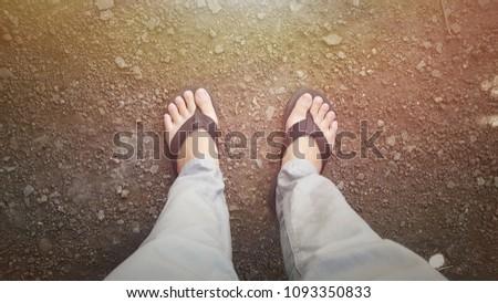 The foot wears black sandals. #1093350833