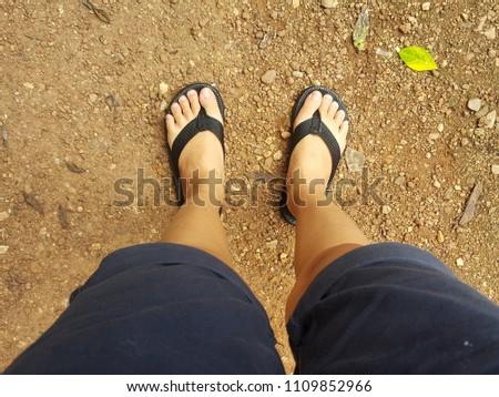 The foot wears black sandals. #1109852966