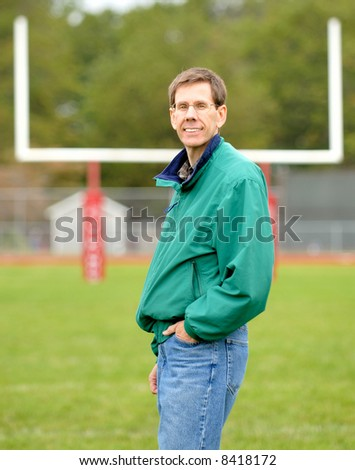 The football coach, standing on a football field with the goalpost behind him.