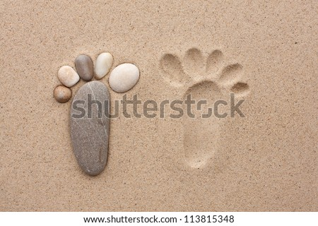 The footprint made up of stones on a sandy background