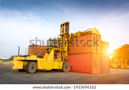 The forklift is lifting the container in the container yard.