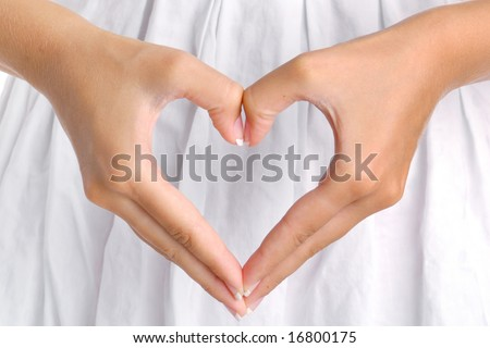 The form of heart shaped by female hands on a white dress background.