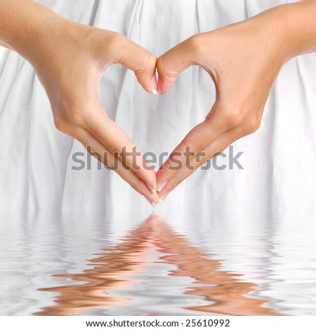 The form of heart shaped by female hands on a white dress background with water reflection.