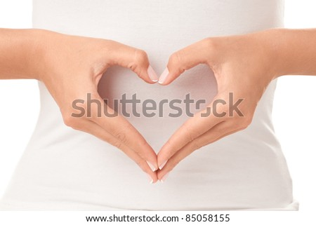The form of heart shaped by female hands on body background isolated on white.