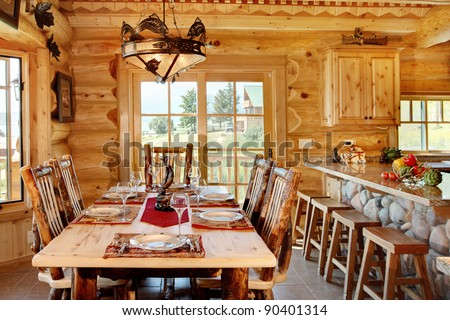 The formal dining room in a modern log cabin. the table is set and ready for an informal meal.